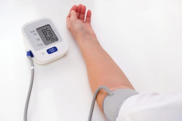 남자는 혈압, 흰색 배경을 측정합니다. 동맥 저혈압. 손과 안압계를 닫습니다.
