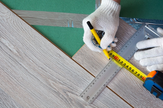 Человек измеряет новый ламинат