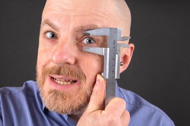 남자는 그의 눈 측정 장치 캘리퍼스의 크기를 측정