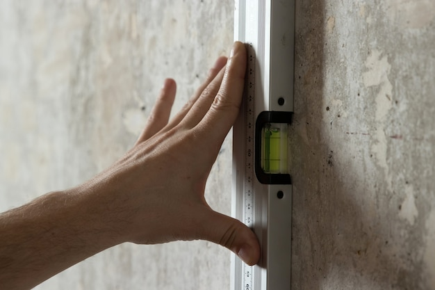 A man measures on the wall with a ruler