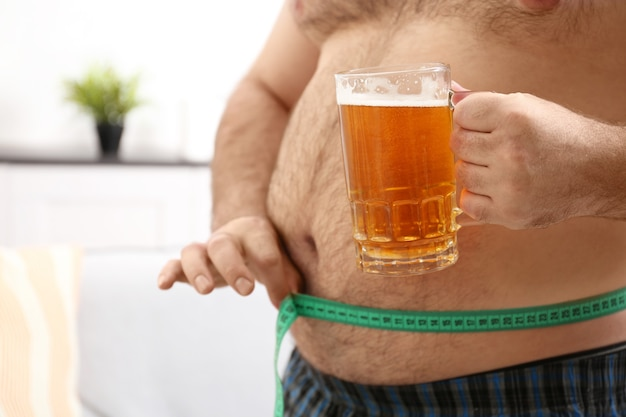 腹を測定し、家でビールのガラスを保持している男