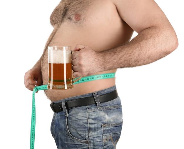 腹を測定し、白い背景の上のビールのガラスを保持している男