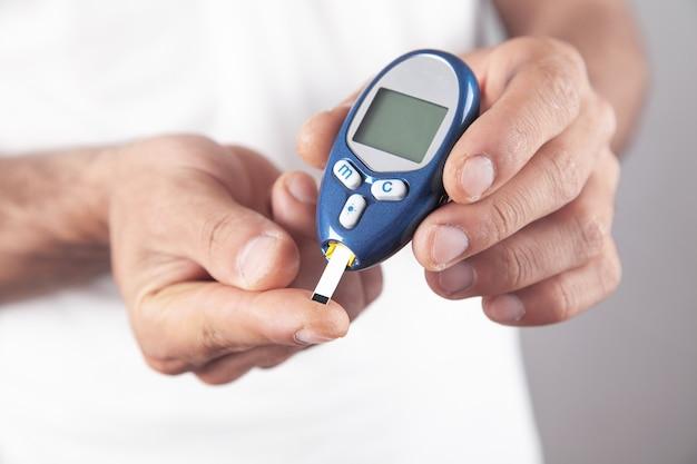 Человек, измеряющий уровень глюкозы дома.