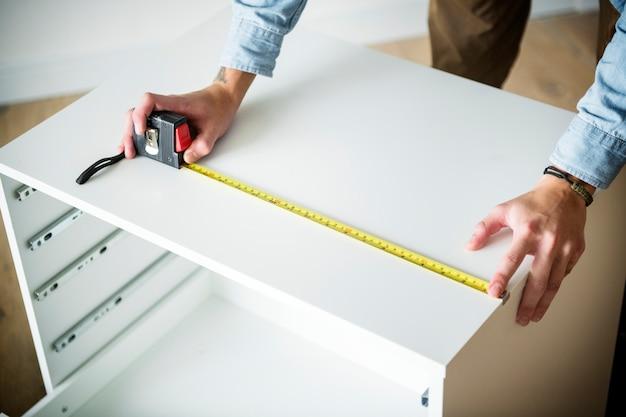 Человек, измеряющий шкаф с измерительной лентой