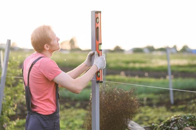 Человек измеряет уровень на ферме