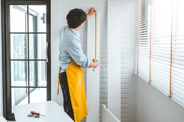 壁を測定する男