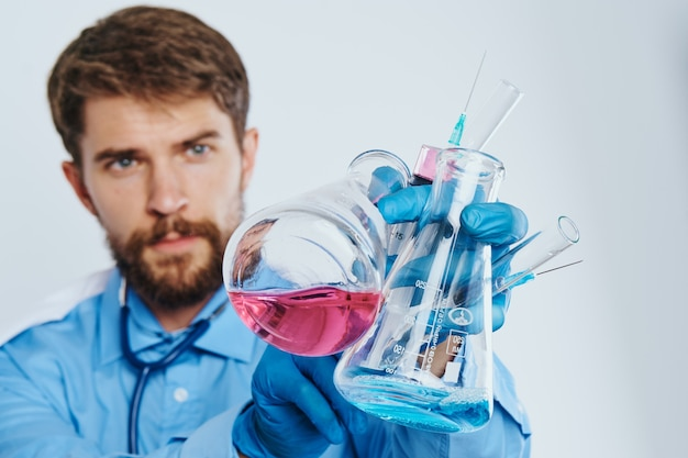Man in medical gown laboratory assistant with liquid in flask and stethoscope doctor chemical reaction light