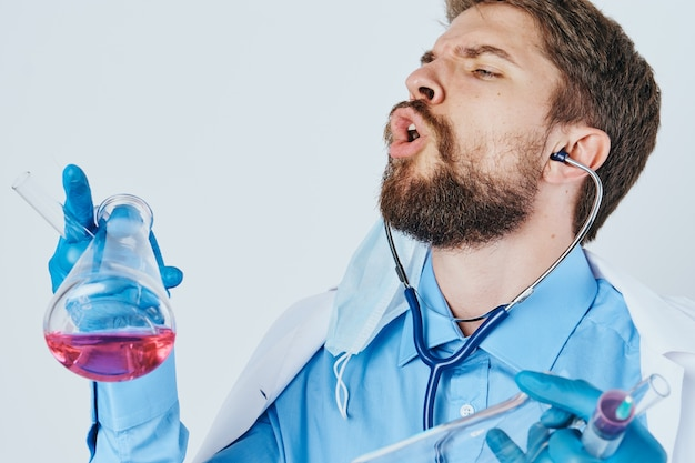 Man in medical gown laboratory assistant with liquid in flask and stethoscope doctor chemical reaction