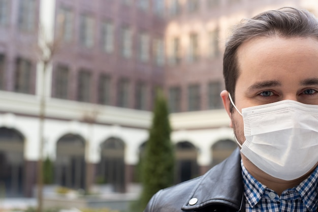 Man in a medical mask on a background of a modern building, coronavirus, illness, infection, quarantine, medical mask