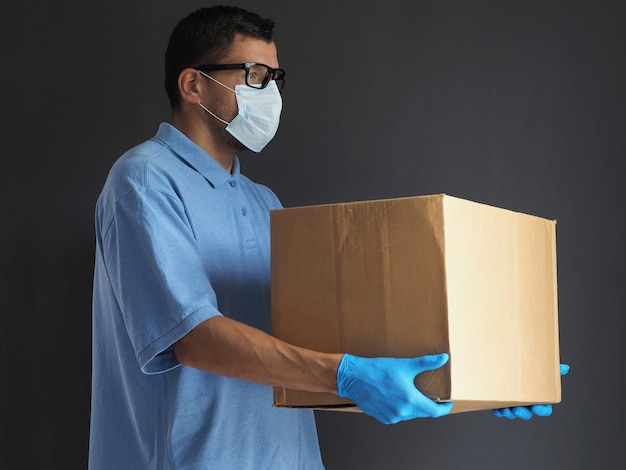Man in medical mask and gloves delivered the parcel. courier with a cardboard box. parcel delivery service during epidemic pandemic coronavirus 2019-ncov, covid-19 virus.