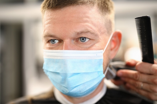 Man in medical mask has haircut in hairdressing salon.