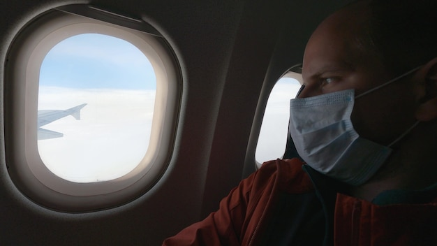 A man in a medical mask looks out the airplane window. safety rules during the coronavirus epidemic. traveling during a pandemic. 4k uhd