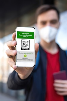 Man in medical mask showing an international vaccination certificate covid-19 qr code on smartphone