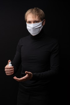 A man in a medical mask shows how to treat his hands with an antiseptic. coronavirus protection.