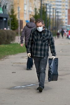 A man in a medical mask on the street, with bags