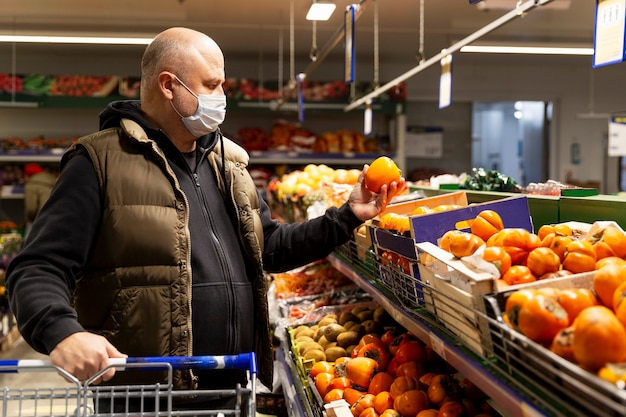 A man in a medical mask in the vegetable section of a supermarket