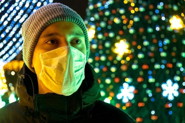 Un uomo in maschera medica e una giacca invernale di notte, decorazione di natale sullo sfondo a chisinau, in moldavia
