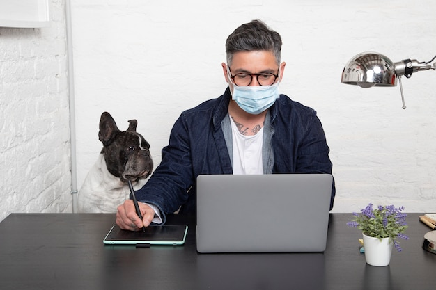 Man in medical mask working on a creative design from home with his dog sitting together in the workspace.