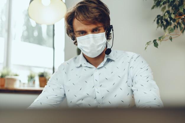 Man in medical mask working from home while coronavirus quarantine