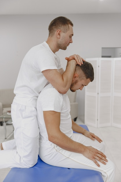 Man in the medical office. physiotherapist is rehabilitating back.