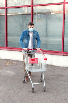 Man in medical protective mask with empty supermarket trolley.