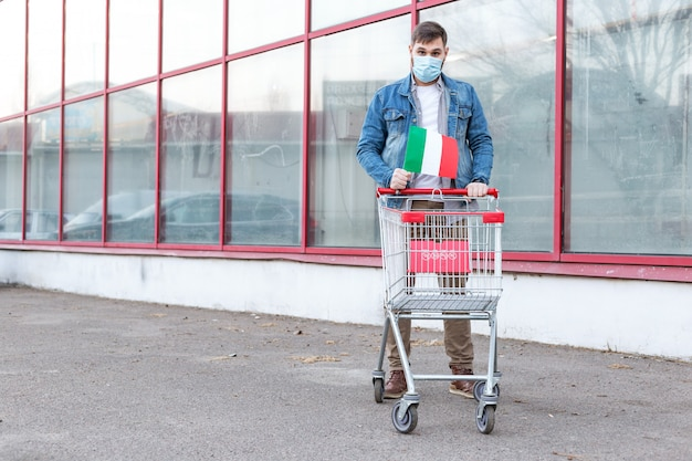 Man in medical protective mask with italian flag and empty supermarket trolley. panic buying food. italy coronavirus spreading outbreak.