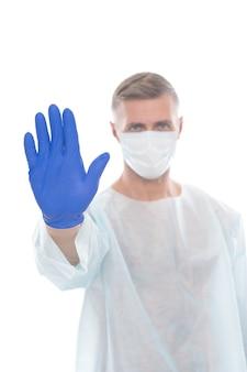男性医療従事者の疫学者がcovid19を停止し、手袋を着用した呼吸器で手振りを示すm