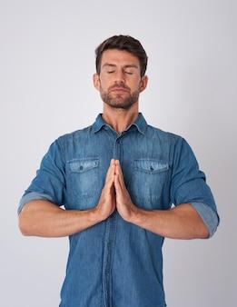 Man meditanting and wearing a denim shirt