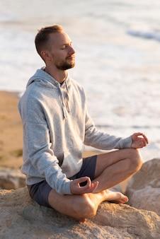 Uomo che medita sulla spiaggia