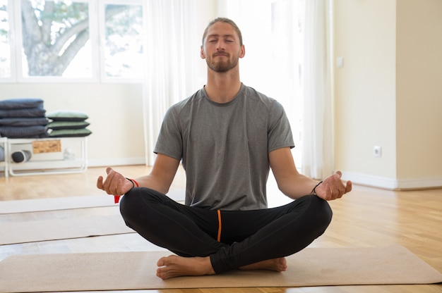 Man meditating and holding hands in mudra gesture in class