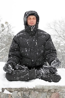 Человек медитирует в позе лотоса зимой