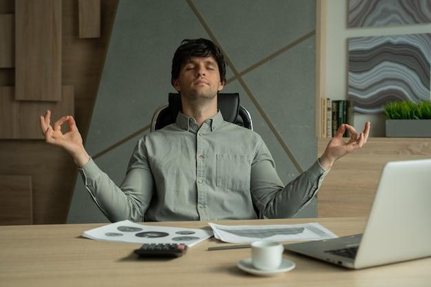 Человек медитирует в офисе, справляется со стрессом, бизнесмен занимается йогой за столом в современном офисе