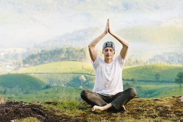 朝、山で瞑想する男。崖の上で屋外でヨガをする。リラクゼーションと健康的なライフスタイル