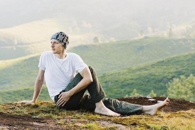 朝、山で瞑想する男。屋外でヨガをする。