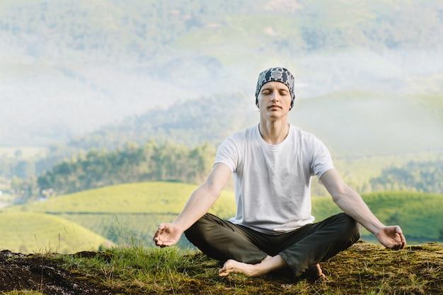 朝、自然の中で瞑想する男。屋外でヨガをする。