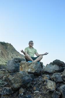 海のそばの岩で瞑想する男