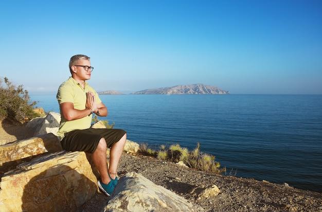 Человек медитирует на горе возле пляжа
