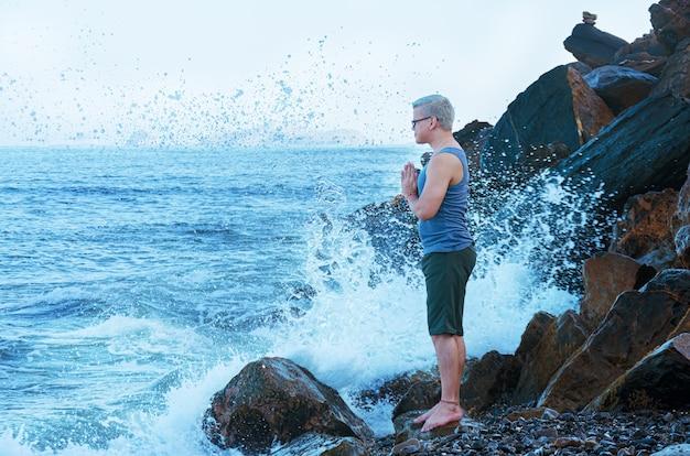 Человек медитирует на берегу моря