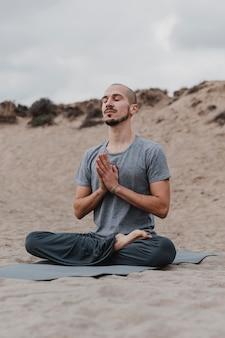 Uomo che medita all'aperto mentre si fa yoga