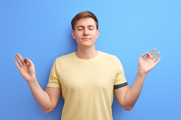Man meditating, stand in yoga pose isolated over blue background. handsome guy is engaged in yoga, stand with eyes closed.
