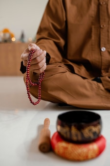 Человек медитирует с бусами рядом с поющей чашей