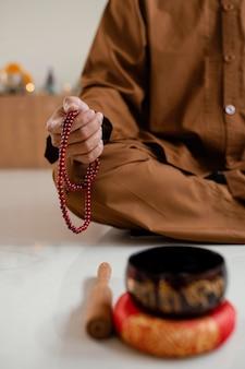 Uomo che medita con perline accanto alla campana tibetana