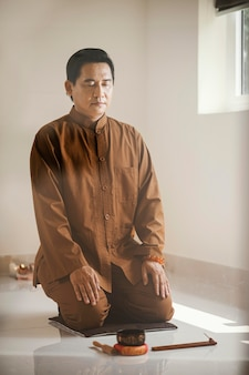 Man meditating with singing bowl and incense