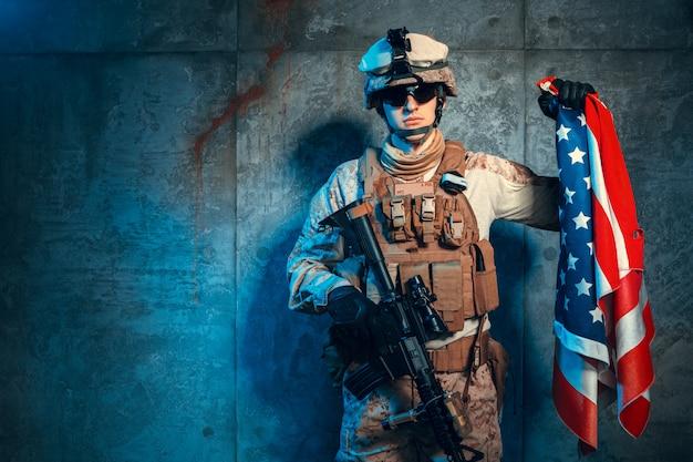 スタジオでアメリカの国旗と現代のman兵兵士の軍服