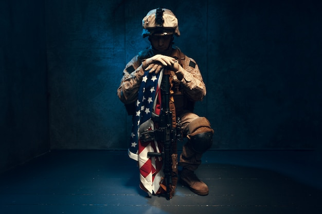 Man military outfit a mercenary soldier in modern times with us flag in studio