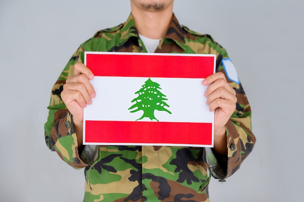 Man in a military shirt holding the flag of lebanon.