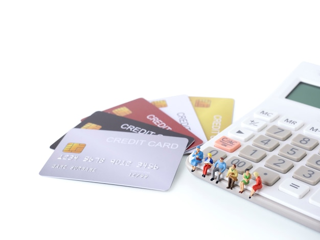 Man miniature figure sit on calculator with stack of credit cards