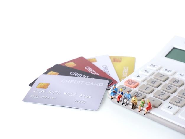 男のミニチュアフィギュアは、クレジットカードのスタックと電卓に座っています