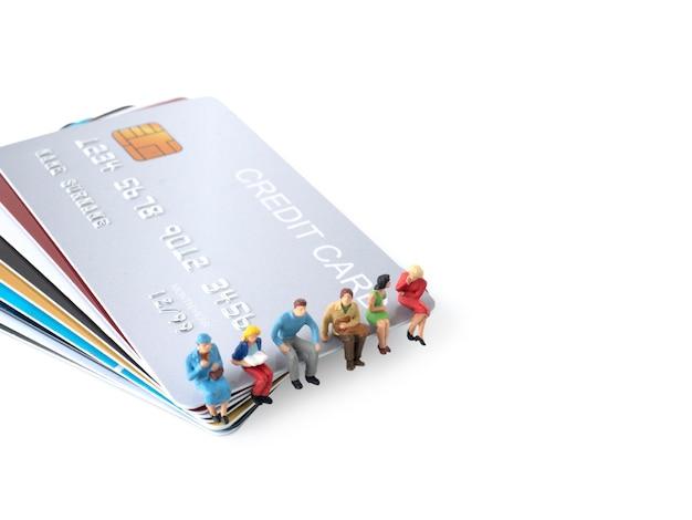男性のミニチュアフィギュアは、クレジットカードの概念によってお金を使うためにクレジットカードのスタックに座っています