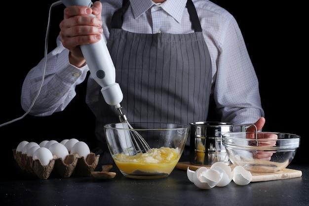 Человек смешивает яйцо в миске, готовит тесто